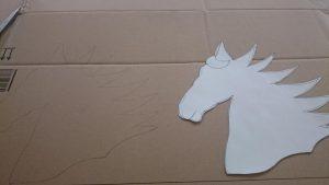 Mit der Schablone den Pferdekopf auf Karton übertragen.